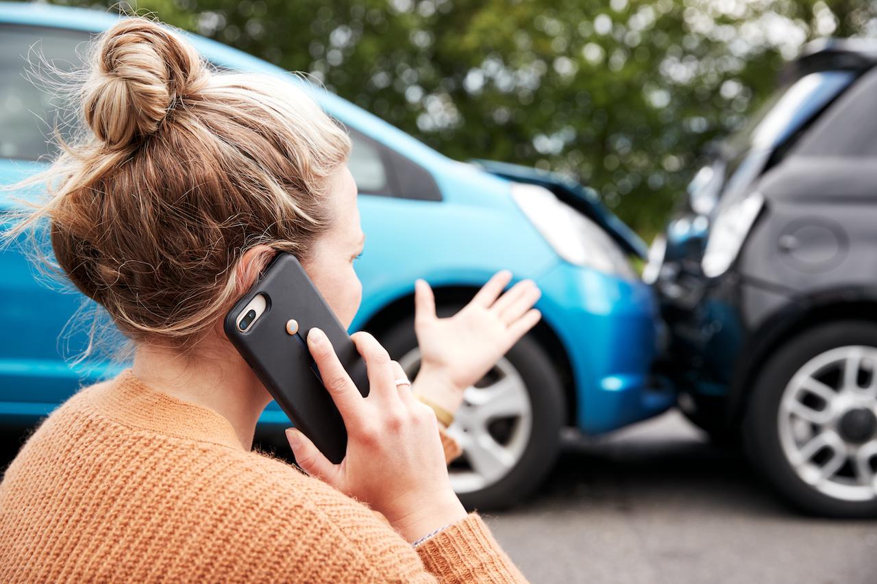 mujer llamando al seguro por choque de auto